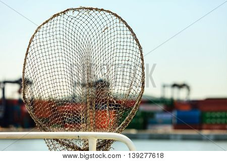 Cargo commerce industry concept.Fishing net in harbour. Fishery tool with containers on pier background.