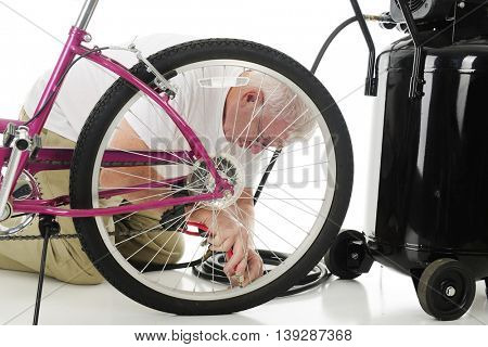 A senior man kneeling beside a girl's bike and an air compressor as he fill's his granddaughter's bike tire with air. On a white background.