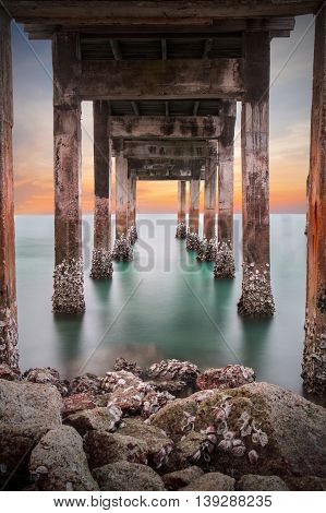 Dark of underneath the pylons of a long jetty pier beach overlooking the sea at sunset or twilight at Khao Laem Ya Mu Ko Samet National Park Rayong Thailand. Seascape long exposure shot