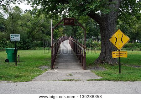 SHOREWOOD, ILLINOIS / UNITED STATES - AUGUST 30, 2015: Pedestrians may cross the Du Page River via the David A. Barry Pedestrian Bridge in Shorewood, Illinois.