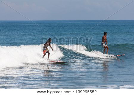 BALI, INDONESIA, 8 April 2016: Surfing in Kuta. Kuta is a beach and resort area in the south of the island of Bali, Indonesia. One of Bali's first tourist developments, it's best known for its Indian Ocean surfing and party-centric atmosphere.