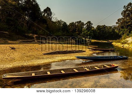 Longboats parked on a stream in the countryside of Laos