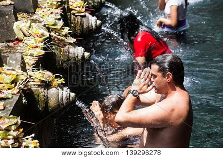 BALI, INDONESIA, 8 April 2016: Praying in Tirta Empul. Tirta Empul temple is a Hindu Balinese water temple located near the town of Tampaksiring, Bali, Indonesia. The temple compound consists of a petirtaan or bathing structure, famous for its holy spring