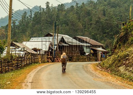 A woman trudges through a village of wooden houses on a snowy day in Laos