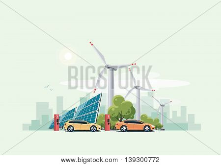 Electric cars charging at the charger station in front of the solar panels and wind turbines. City skyline in the background.