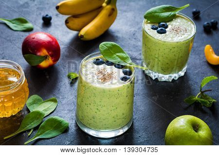 Detox green smoothies. Still life of green smoothie with fruits, honey and spinach leaves. Ultra healthy detox green smoothie with spinach, chia seeds, bananas, green apple, plain yogurt and honey on slate background