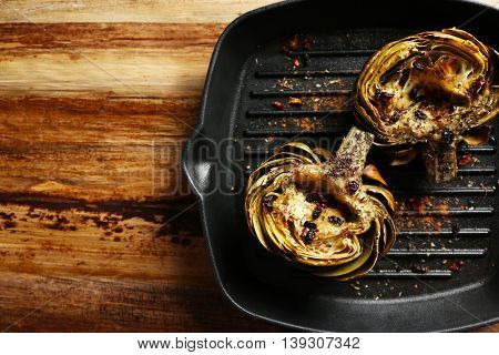 Baked artichokes in black grill pan on wooden background