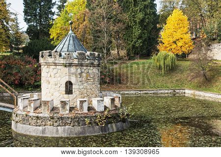 Turret in Bojnice autumn park lake and colorful trees. Slovak republic. Seasonal natural scene with beautiful pond.