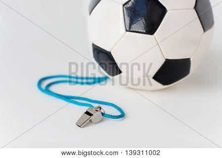 sport, soccer, football, refereeing and sports equipment concept - close up of ball and referee whistle