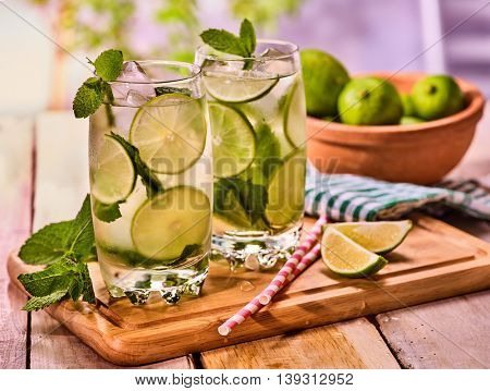 Alcohol country cocktail. On wooden boards two glasses with alcohol cocktail and ice cubes. Drink hundred ninety cocktail mohito with straw and lime bowl and mint leaf. Country outdoor.