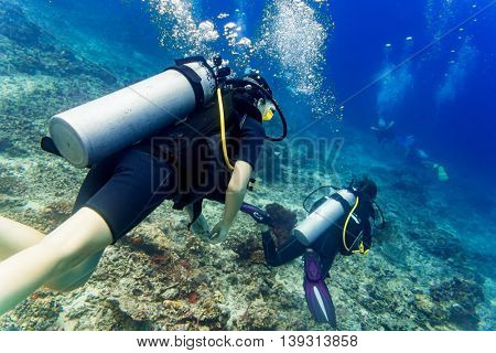 Two divers scuba diving in tropical sea at reef
