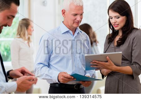 Business women and men in office looking at presentation in a standup meeting
