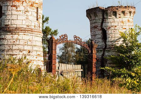 Metal doors with decorative elements and dilapidated towers at the entrance of an old castle