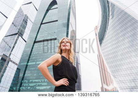 Portrait of confident blonde woman in black style clothes with arms akimbo