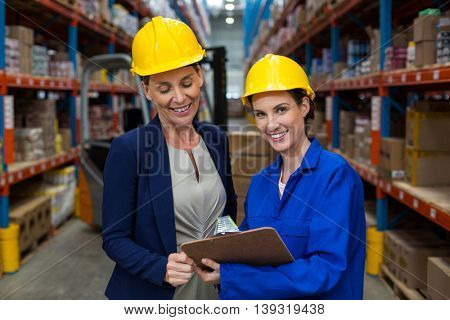 Female smiling coworkers looking at clipboard in warehouse