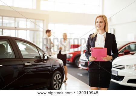 Professional beautiful salesperson working in car dealership