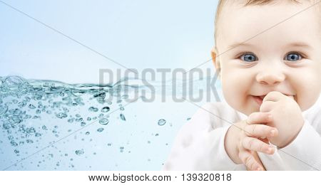 people, babyhood, child care and advertisement concept - close up of happy baby boy over blue background with water splash