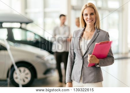 Professional young beautiful salesperson at car dealership