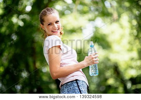 Dehydrated young cute female jogger drinking water