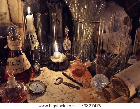 Still life with vintage bottles, key, magic objects and parchments. Old pharmacy, medieval alchemy or witch laboratory, alchemist or homeopathic ritual, spell with occult and esoteric symbols