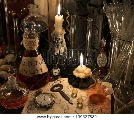 Close up with vintage clock, key, candles, bottles and magic objects. Old pharmacy,  medieval alchemy laboratory, alchemist or homeopathic ritual, spell with occult and esoteric symbols