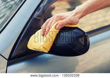 waterless car wash. Men's hand with yellow cloth cleaning car photo with toning. Washing the car by hand with rag. Cleaning the car. Car care concept. Hand of man washing the car using the sponge