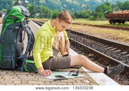 man sitting with map and travel bag at the train station. Traveler holding map waiting for a train at train station and planing for next trip by mobilephone.