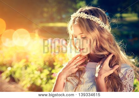 Charming Bride with Wedding Tiara on Warm Nature Background. Modern Bridal Style. Candid Image. Toned Photo with Bokeh and Copy Space.