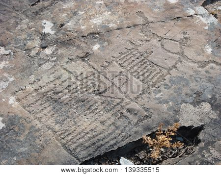 Stone with prehistoric building picture. Prehistorical petroglyphs carved in rocks. Siberian Altai Mountains Russia