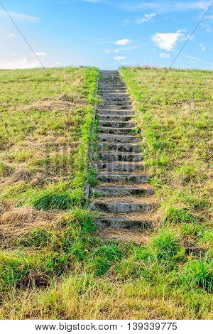 Concrete stairs to the top of a dike in the Netherlands. On the steps is yellowed grass. It's a sunny day in the summer season.