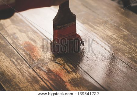 Craftsman Hand Painting Brown Color On Wooden Table