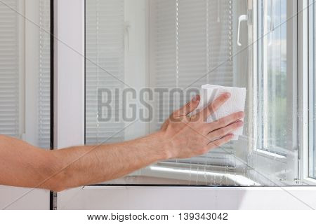 Houseworker clean plastic pvc window with napkin