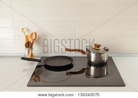 Open saucepan pan and wooden spoons in modern kitchen with induction stove