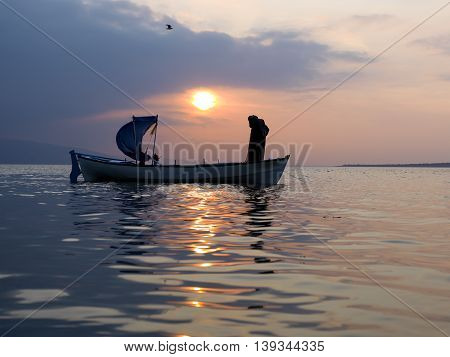 fisherman throught net to lake for fishing on sunet time