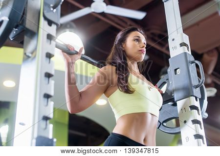 Fit woman doing squats with the barbell Smith machine in the gym poster