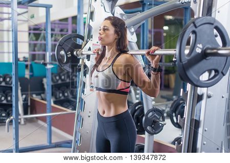 Fit woman doing shoulder press exercise with a weight bar Smith machine at gym poster