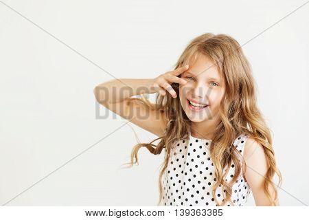 Lovely Little Girl In A Polka-dot Dress Against A White Background