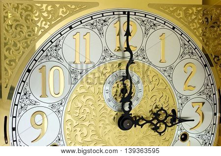 ornate brass engraved grandfather clock face with arabic numerals and hands on three o'clock