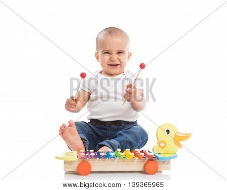 Smiling baby child playing metallophone isolated, close up