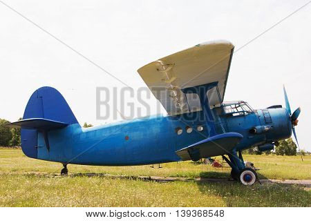 Blue Biplane on the airfield. Summer. Side view.