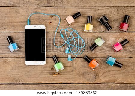 Bottles Of Colorful Nail Polish, Smart Phone And Headphones On Brown Wooden Table