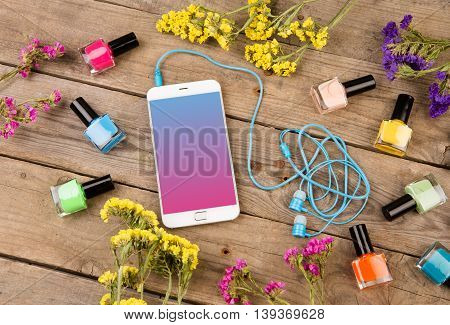 Bottles Of Colorful Nail Polish, Smart Phone, Headphones And Flowers On Brown Wooden Table