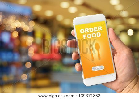 Woman hand holding smartphone against blur colorful bokeh background with food online concept