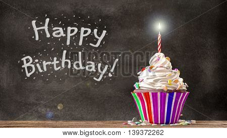 Cupcake with cream candies and a candle on a wooden table with Happy Birthday written on a blackboard background. Empty free copy space available. 3D Rendering