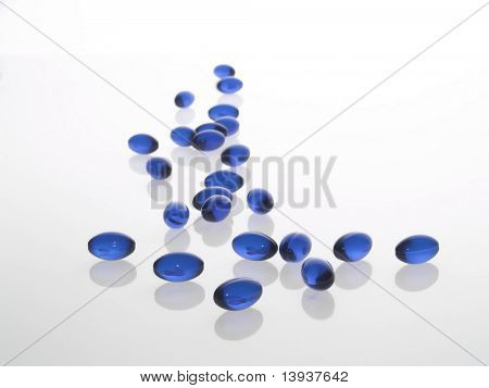 Blue medical capsules on gray background