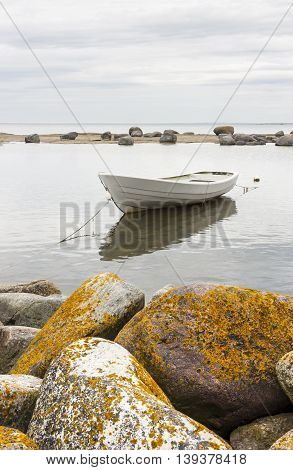 White oaring boat behind large round rocks on a cloudy day