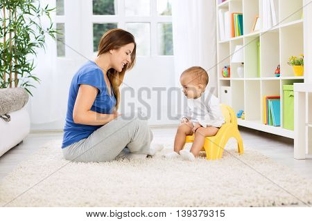 Beautiful Mother Learning Little Child How To Sitting On Potty