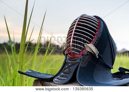 Used and Dirty Kendo Helmet or Men in grass field on sunset background.