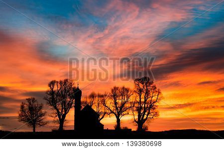 Early morning sunrise dawn with black silhouette of small church or chapel and bare trees on colorful cloudy flaming sky background