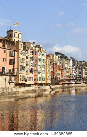 GIRONA SPAIN - MAY 15 2016 :Colorful houses on the river Onyar and tourists on the Princess Bridge. Girona is one of the major Catalan cities.It has one of the largest historical Jewish quarters in Europe.